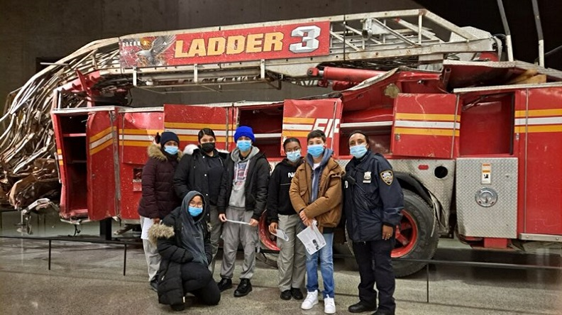 A group of young people wearing masks pose alongside an NYPD officer in front of the Ladder 3 firetruck in the 9/11 Memorial Museum.