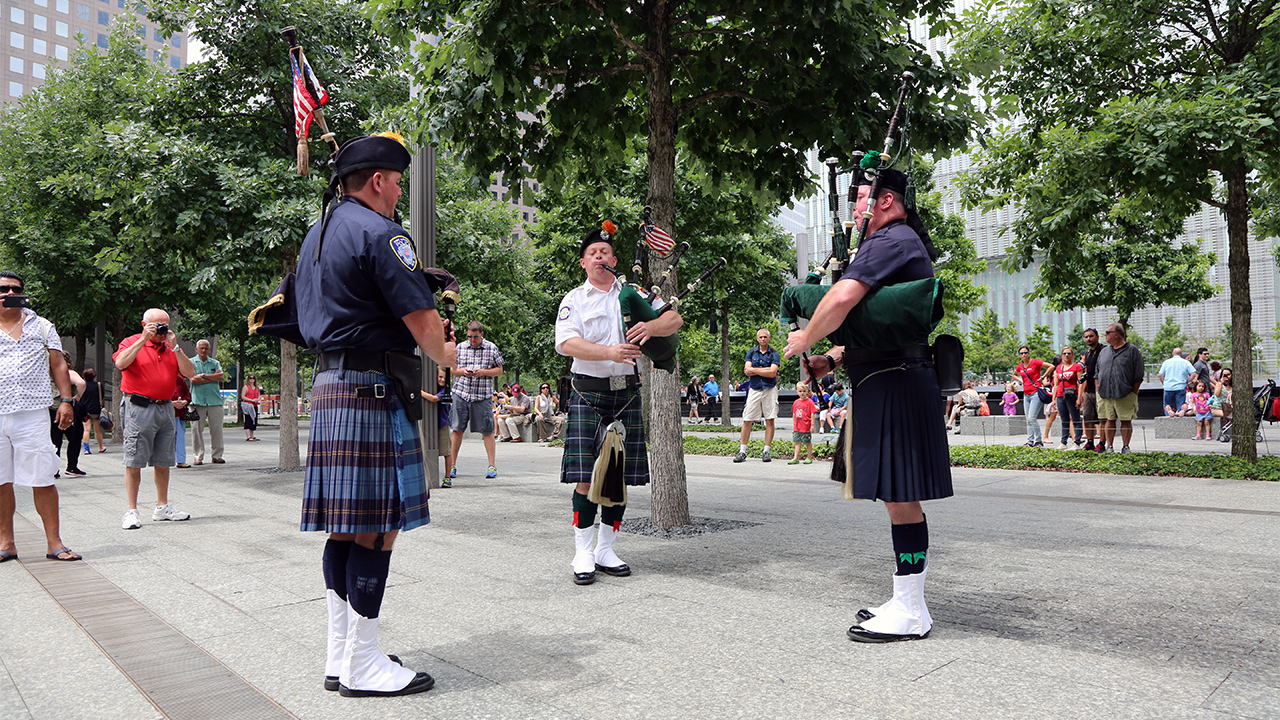 Three men wearing kilts stand in a circle while playing bagpipes on the 9/11 Memorial Plaza in daytime.   Visitors to the Memorial are standing on the periphery, listening to the music.  Two people are taking photos of the bagpipers.
