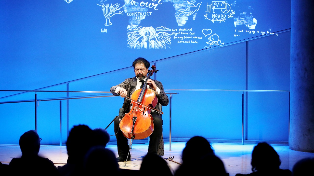 Cellist Karim Wasfi performs while seated onstage in this wide-angle photo of the Museum Auditorium. His bright orange-brown cello contrasts with the blue lights of the stage. The silhouettes of audience members are visible in the foreground.