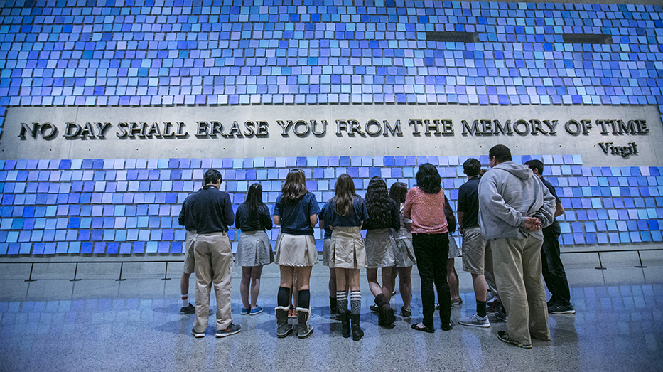 "A group of students in school uniforms looks up at a large inscription on the wall that reads ""No day shall erase you from the memory of time."" The quote from Virgil's epic poem The Aeneid is surrounded by 2,983 unique blue tiles that comprise ""Trying to Remember the Color of the Sky on That September Morning"" by Spencer Finch."