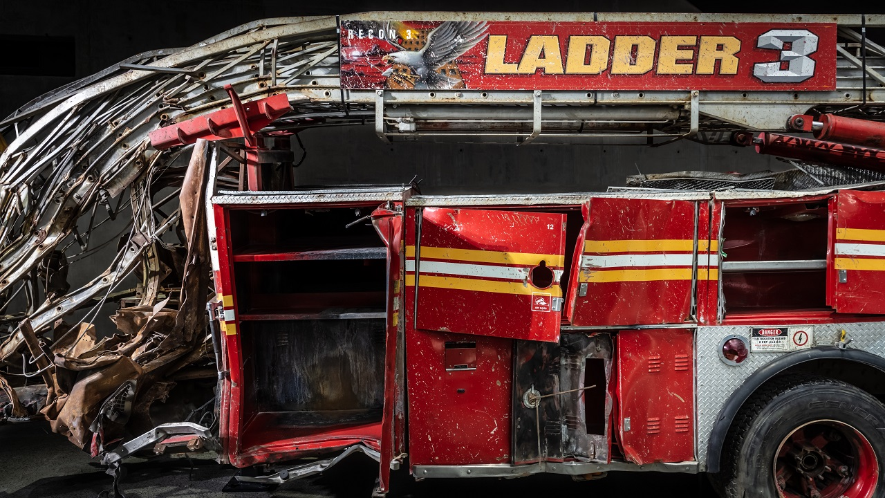 The heavily damaged firetruck of Ladder Company 3 sits in the Museum. This close-up view shows the bright red vehicle's twisted ladder and broken compartment doors.