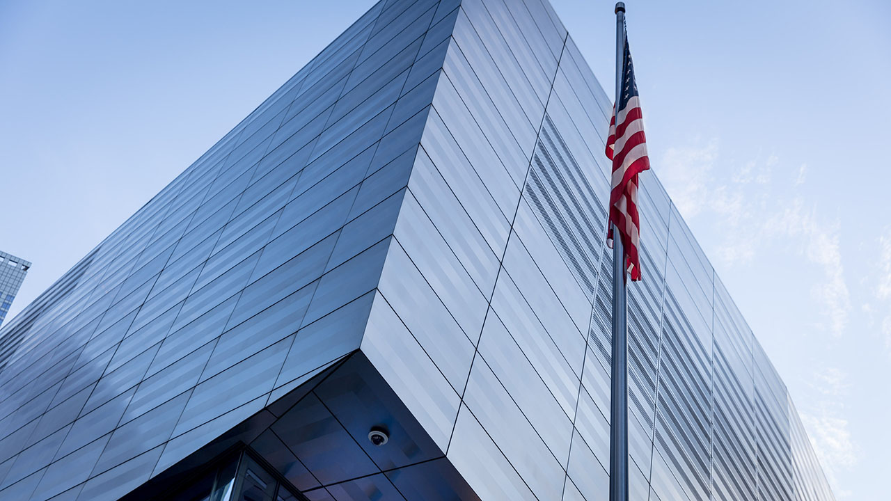 A corner of the two-story, glass and steel Museum Pavilion reflects the light blue sky. An American flag is on a pole to the right.