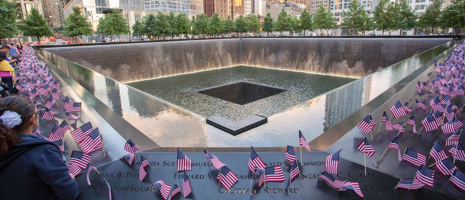Small American flags line the bronze parapets that surround the Memorial pool where the South Tower once stood. The flags have been placed at the names of victims.