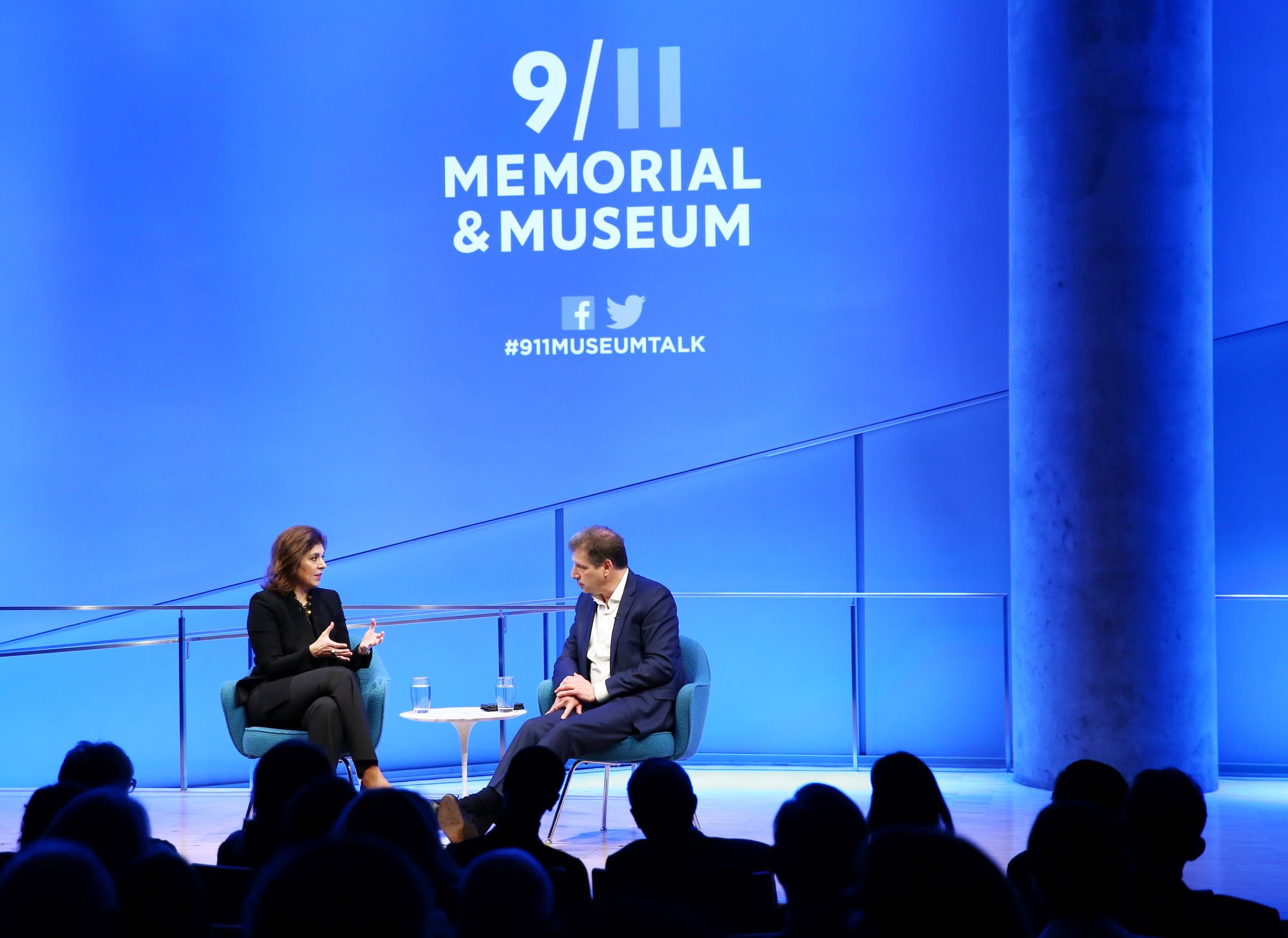 Author Farah Pandith gestures as she speaks with Foreign Affairs editor Gideon Rose onstage at the Museum auditorium. The silhouettes of audience members are visible in the foreground. The stage is lit up blue and white and the logo for the 9/11 Memorial & Museum is projected above Pandith and Rose. Audience members are silhouetted in the foreground.