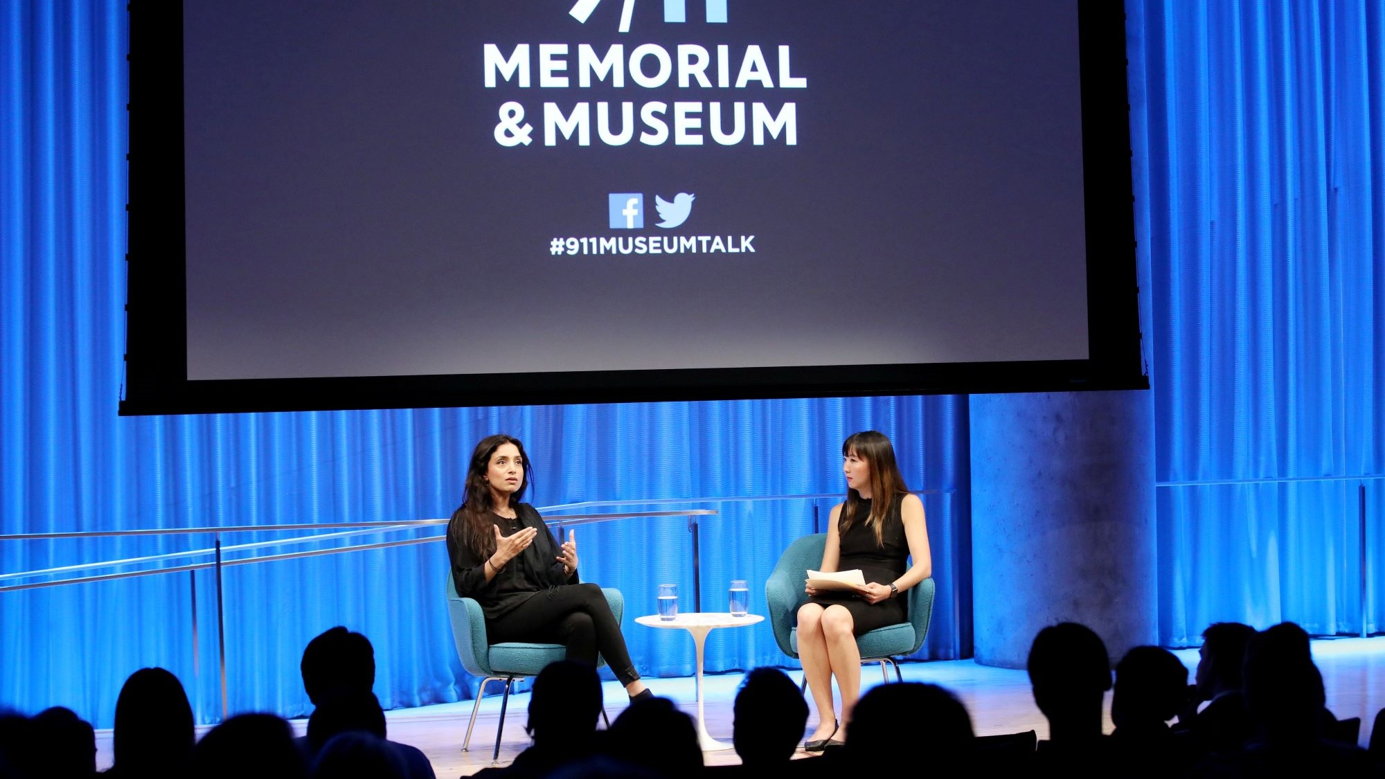 Emmy Award–winning documentarian Deeyah Khan speaks with a woman onstage during a public program at the Museum Auditorium. Khan gestures with both hands as she looks out towards the audience, who are silhouetted by the stage lights. A large projection screen has been lowered above her and the woman hosting the event.
