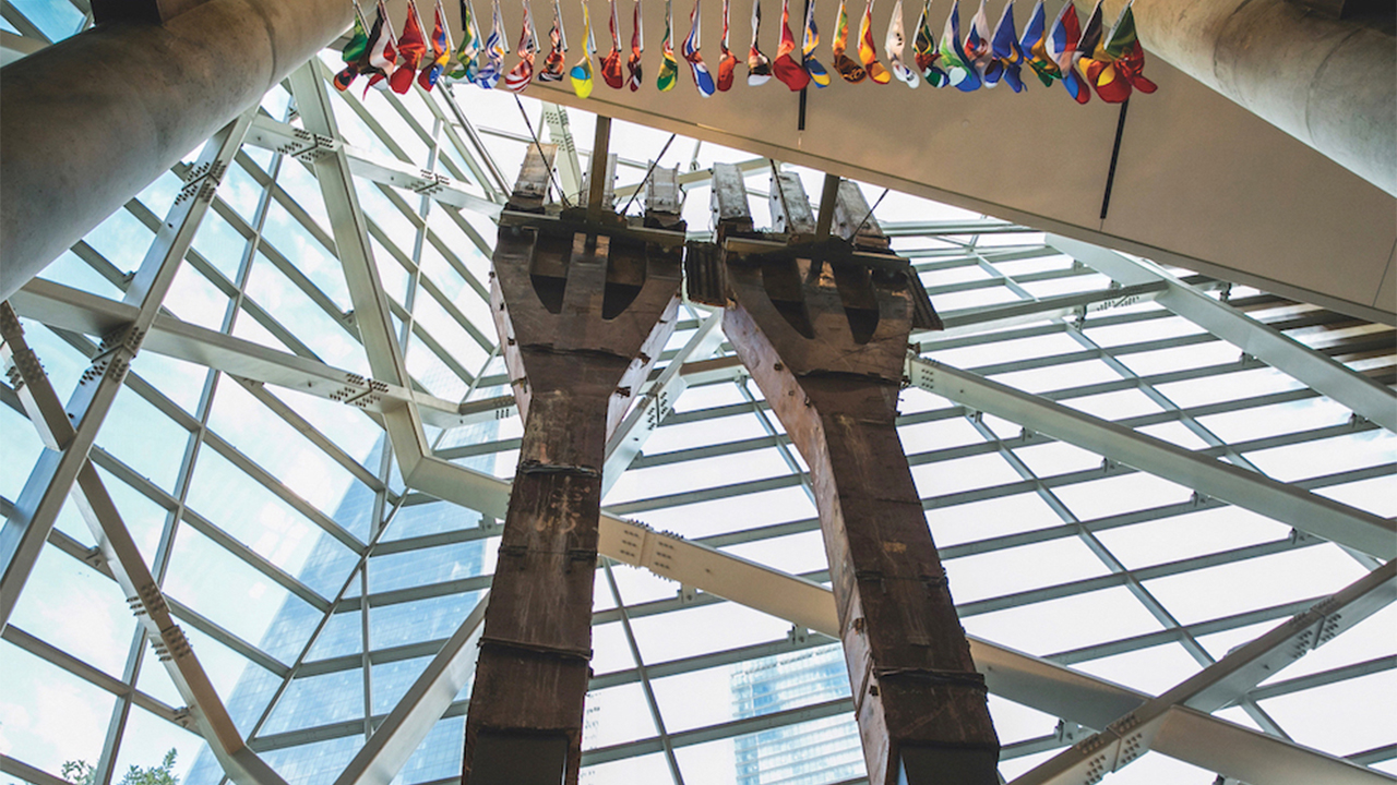 Two 80-foot-tall steel columns, known as the Tridents, tower over the interior of the museum Pavilion. One World Trade Center points skyward outside the windows.