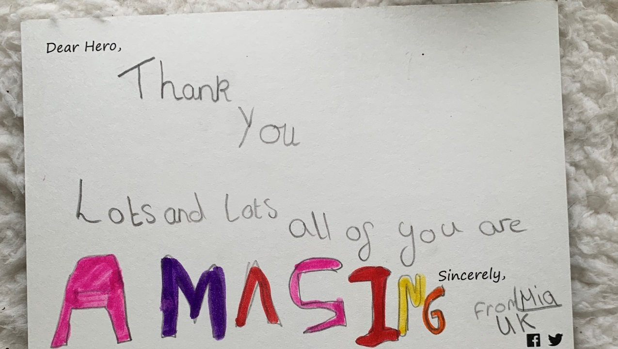 "'Dear Hero' card features a handwritten message by Mia, a child from the UK. The card reads, ""Thank you lots and lots. All of you are amazing."""