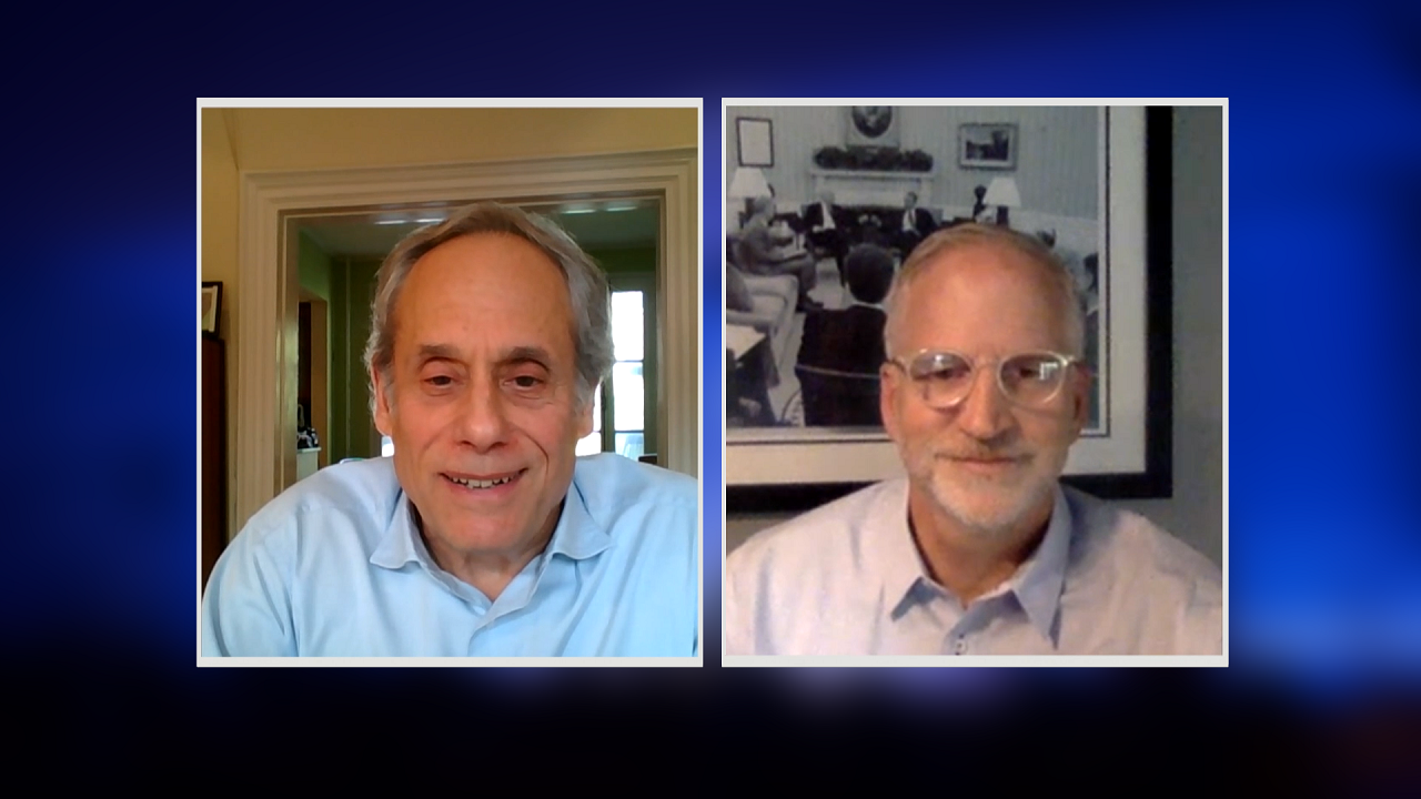 A screenshot from a video conference call shows two men with graying hair. A man to the left of the frame is listening intently with his hands clasped in front of him. To the right, a man in glasses is speaking.