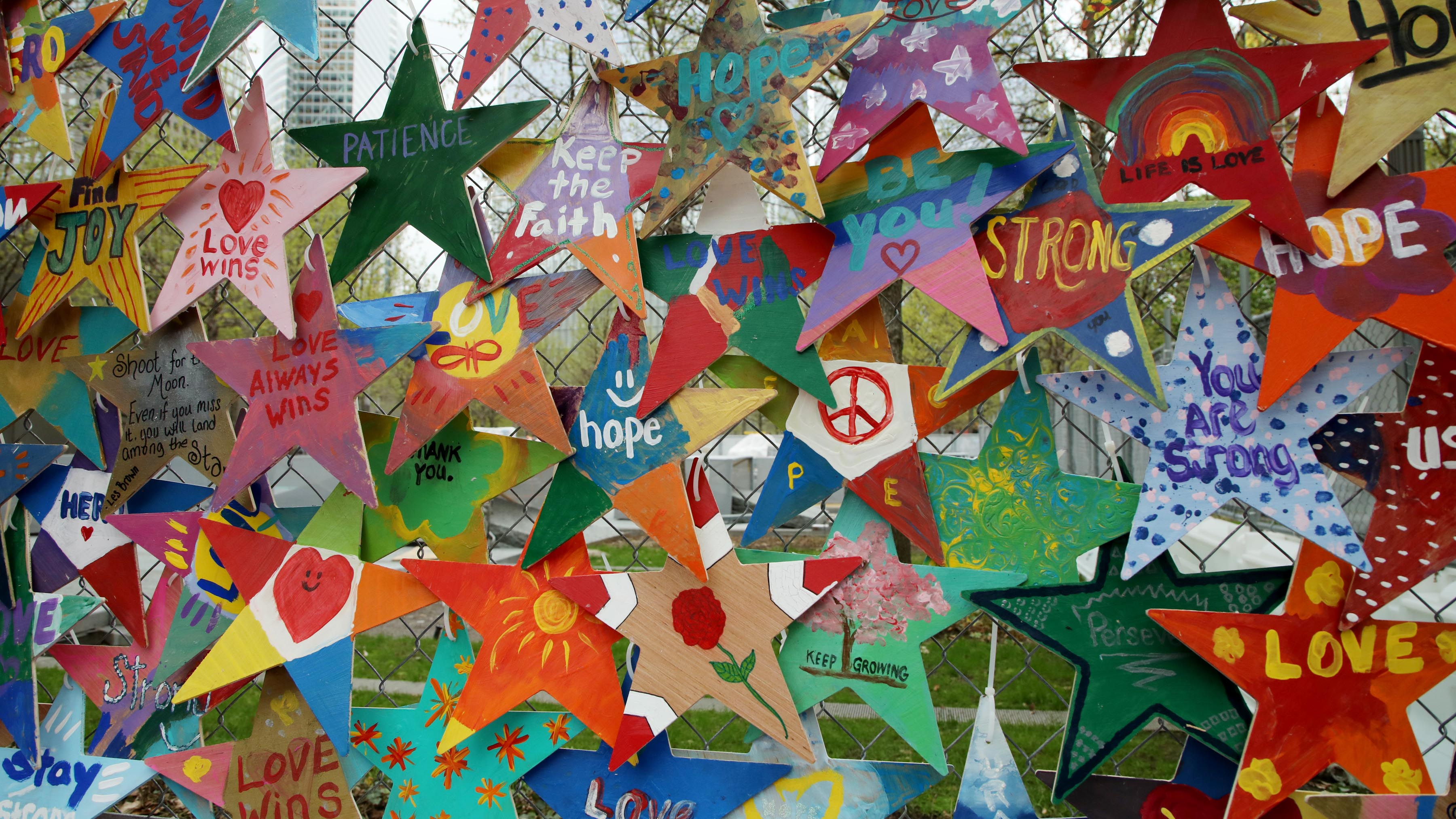 "An array of hand-crafted Stars of Hope decorate a fence near the 9/11 Memorial plaza.  The stars bear messages such ""Peace,"" ""Keep the Faith,"" and ""Love Wins."""