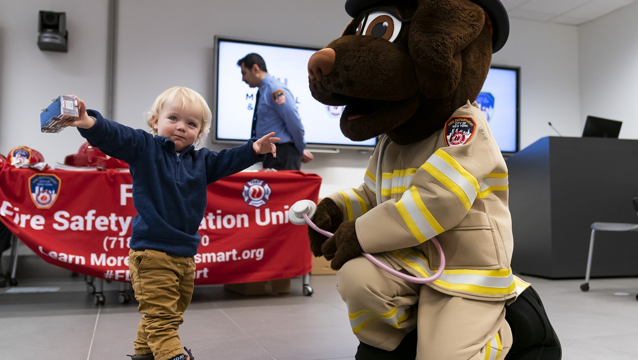 A person in a FDNY Fire & Life Safety dog mascot suit greets a young visitor, whose arms are outstretched.
