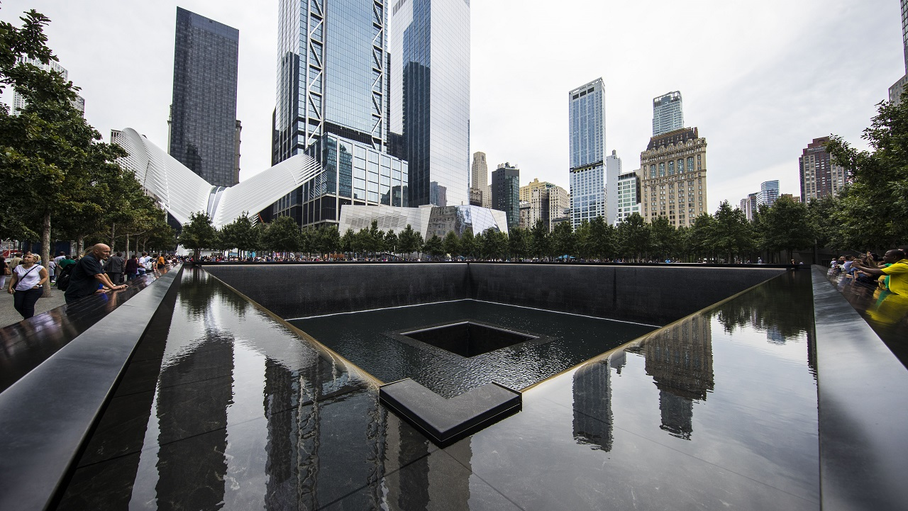 The surrounding buildings of the World Trade Center site are seen reflected in the memorial pool on an overcast day.