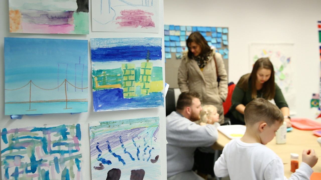 This photograph frames children's artwork and children working on an art activity in the Museum's classroom space.