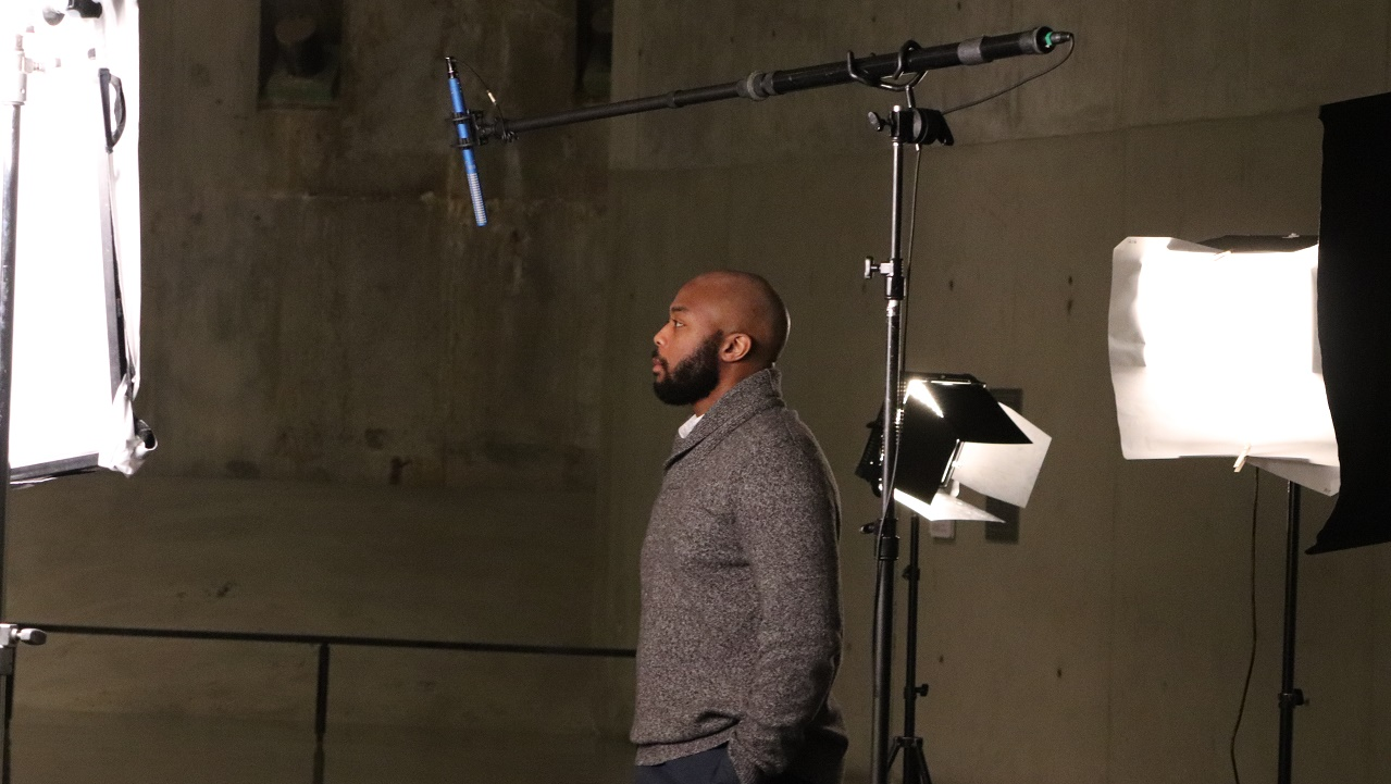 In this photograph, a man stands in profile before a boom mic and set lights during the Anniversary in the Schools webinar filming.