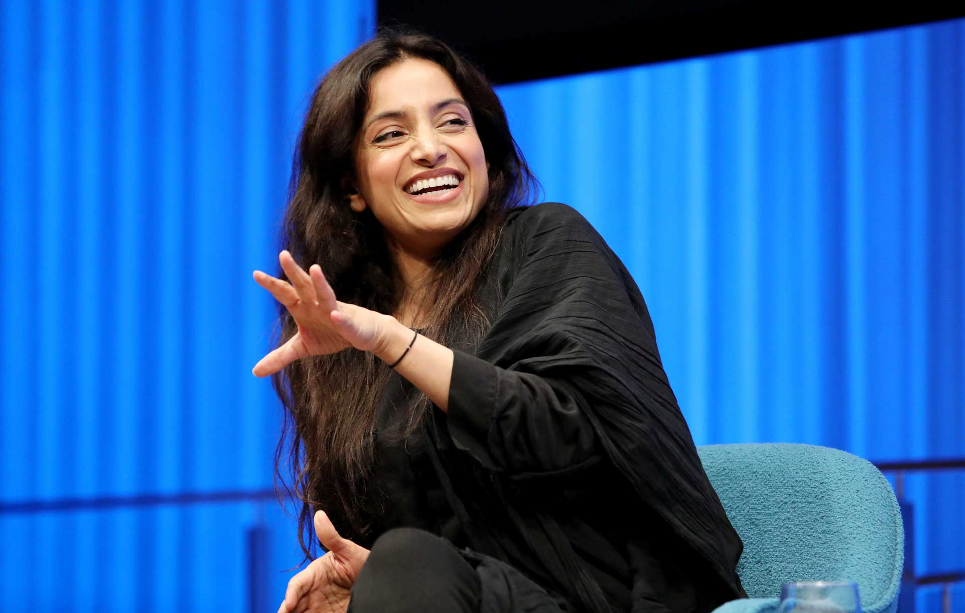 Emmy Award–winning documentarian Deeyah Khan smiles as she leans forward and gestures with her left hand onstage while speaking during a public program at the Museum Auditorium. Curtains behind her are lit up blue.