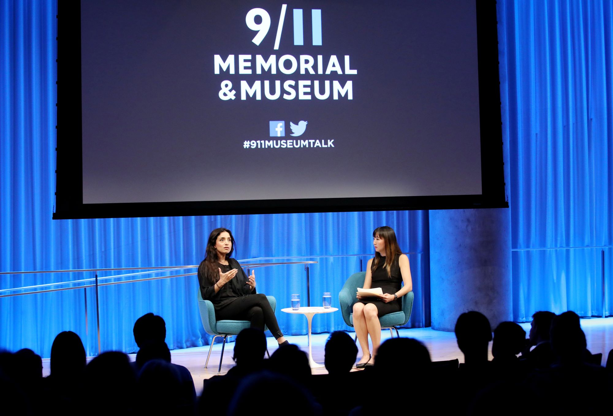 In this wide-angle photo of the Museum Auditorium stage, Emmy Award–winning documentarian Deeyah Khan speaks to the audience while seated next to a woman hosting the event. The audience members are silhouetted by blue and white lights shining on the stage. A large projector screen has been lowered above the two of them.