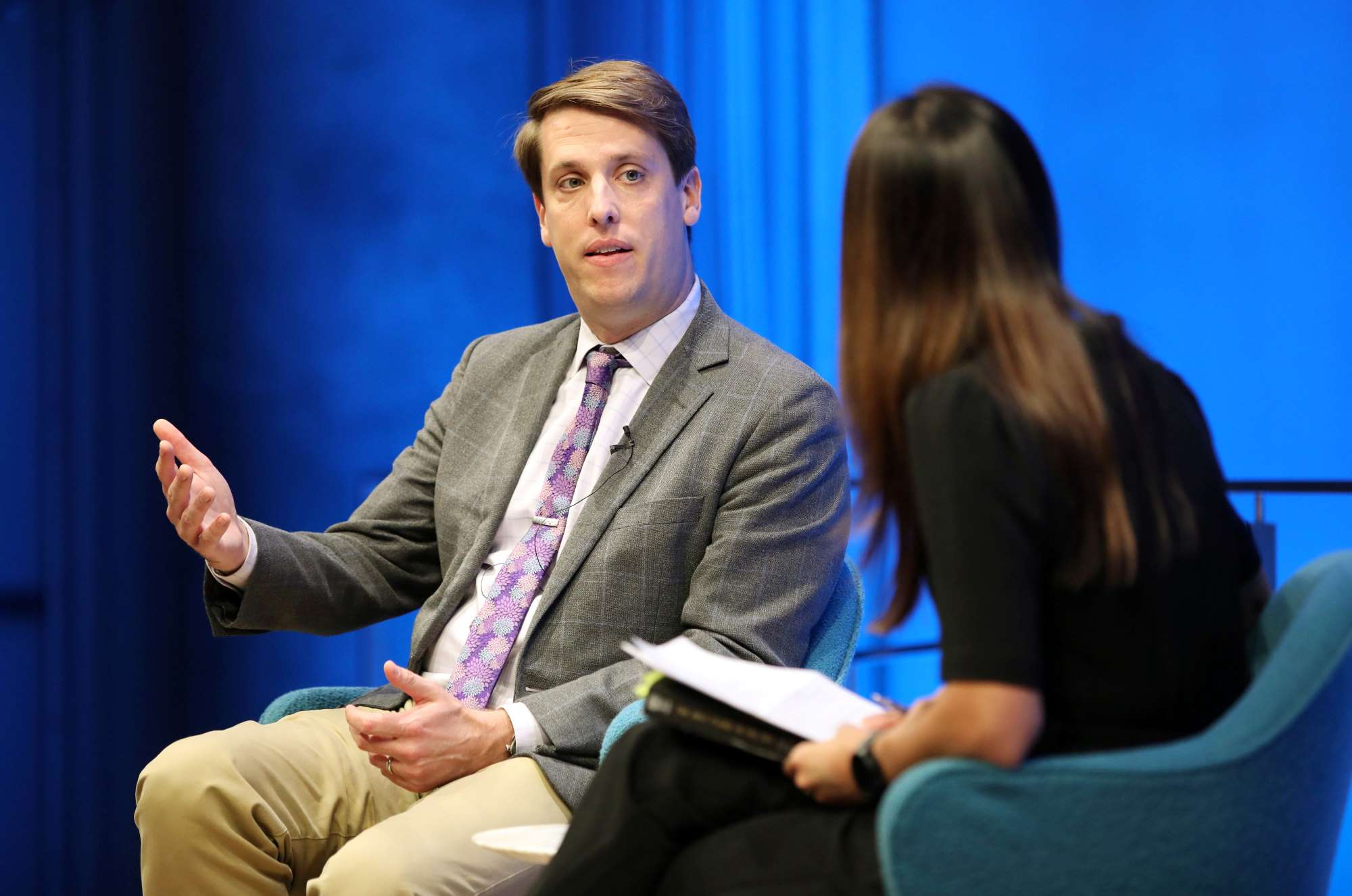 Journalist and historian Garrett Graff gestures with his right hand as he speaks while seated onstage in this close-up photo of him and the host, who is seated beside him in the foreground.