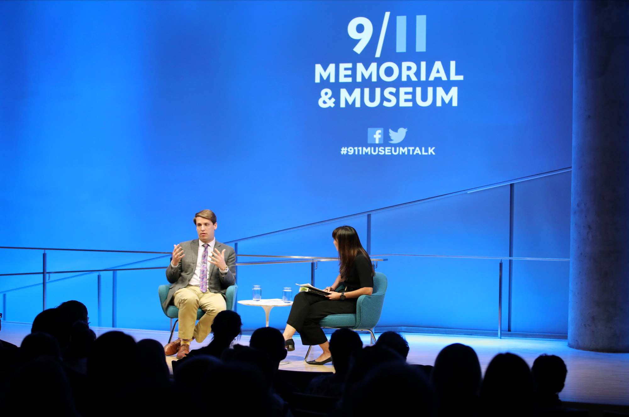 "This wide-angle photo of the Museum Auditorium shows journalist and historian Garrett Graff seated onstage with the woman who is hosting the public program ""Only Plane in the Sky. Graff is gesturing with both hands as he looks towards the audience, whose heads are silhouetted in the foreground. A wall behind Graff is lit blue and features the logo of the 9/11 Memorial & Museum."