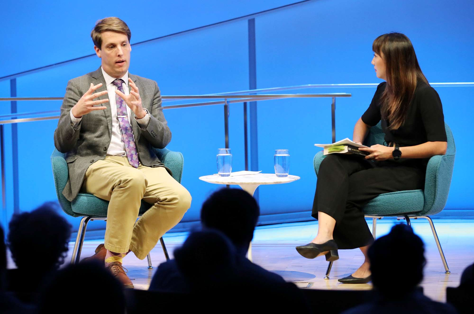 "Journalist and historian Garrett Graff gestures with both hands as he speaks onstage during the public program ""Only Plane in the Sky."" A woman hosting the program sits next to him as she watches on and holds a pile of papers and books. The silhouetted heads of several audience members are in the foreground."
