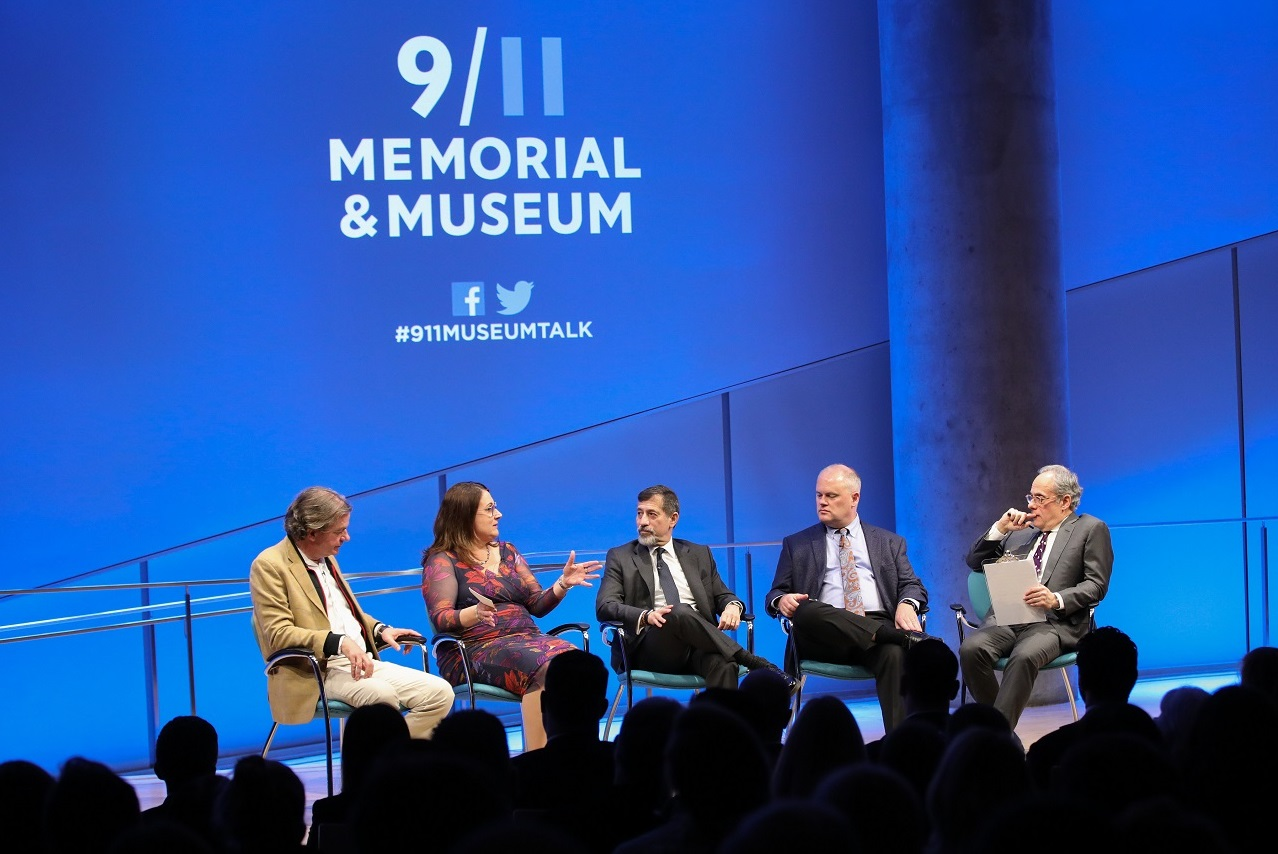 This wide-angle photo of the Museum Auditorium stage shows five people seated as they take part in a public program. Al-Qaeda expert Mary E. Galligan, sitting second from the left, speaks as the other attendants listen on. Al-Qaeda expert Peter Bergen sits to her right. Three other men are seated to her left—al-Qaeda expert Bruce Hoffman, Museum advisor Mark Stout, and Clifford Chanin, the executive vice president and deputy director for museum programs. About a dozen audience members watch on in the foregr
