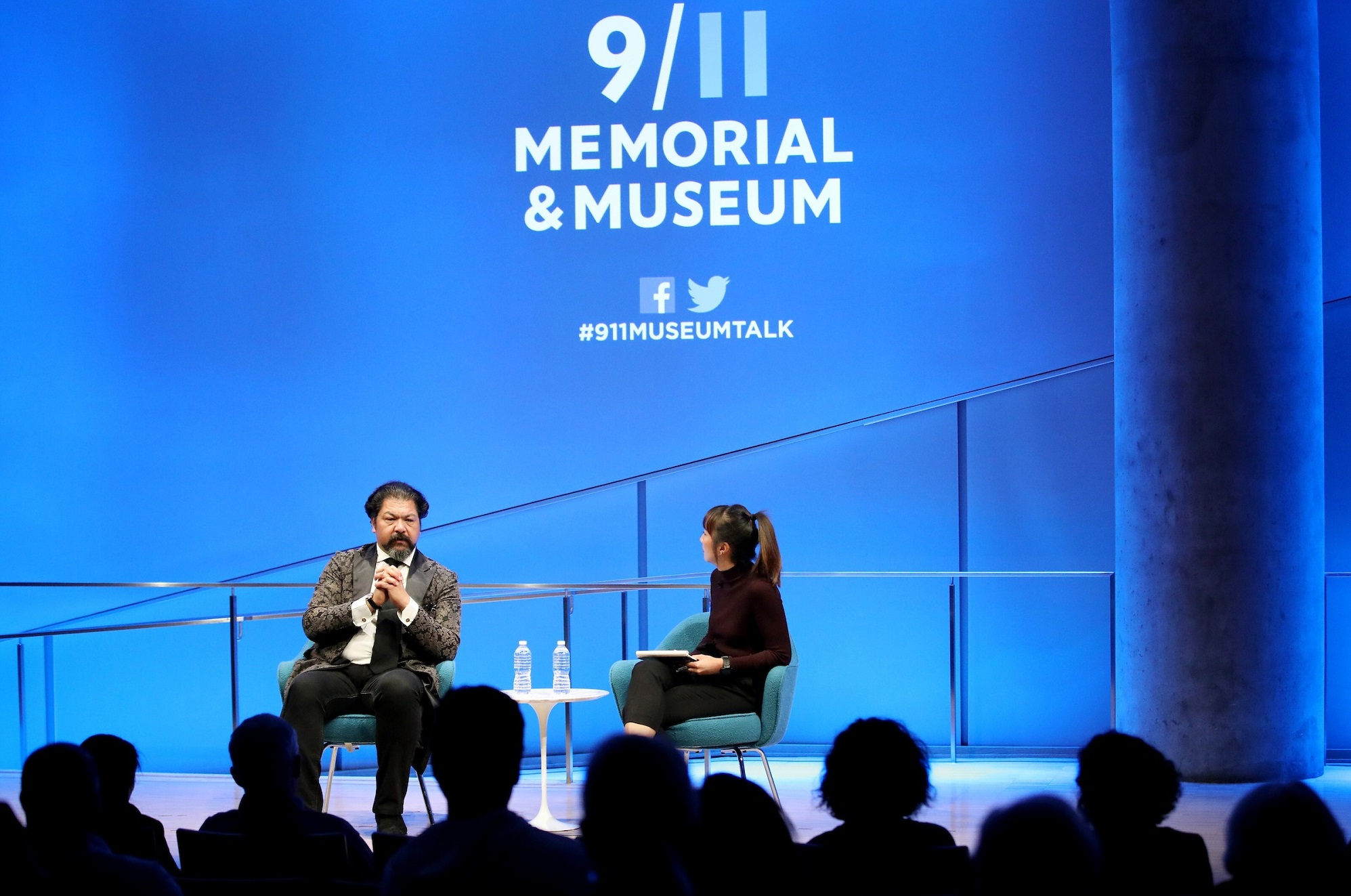 This wide-angle photo of the Museum Auditorium shows Cellist Karim Wasfi and a woman hosting the event seated onstage in the distance. Wasfi has his hands clasped together as he speaks. A wall behind the two participants is lit blue and features the logo of the 9/11 Memorial & Museum.