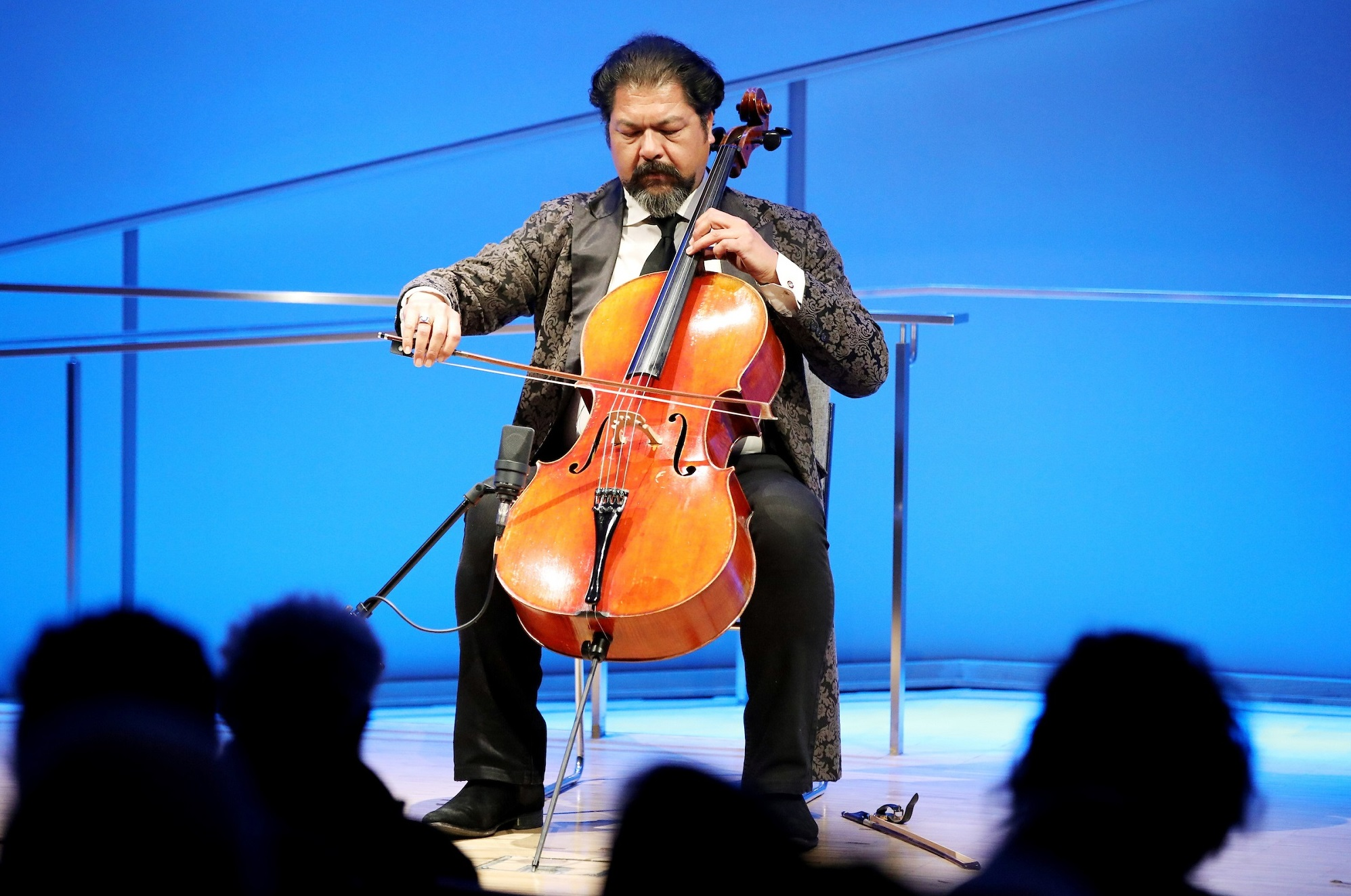 Cellist Karim Wasfi performs while seated onstage at the Museum auditorium. His eyes are closed as if he's concentrating. His right hand grasps the bow as his left hand moves along the strings. His bright orange-brown cello contrasts with the blue lights of the stage. The silhouettes of several audience members are visible in the foreground.