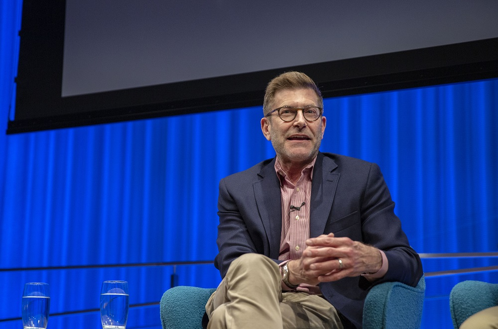 Ken Lustbader, the former advisor to the Lower Manhattan Emergency Preservation Fund, speaks while seated onstage at the Museum Auditorium. He is looking out at the audience with his hands clasped and his legs crossed. A curtain in the background is illuminated blue.