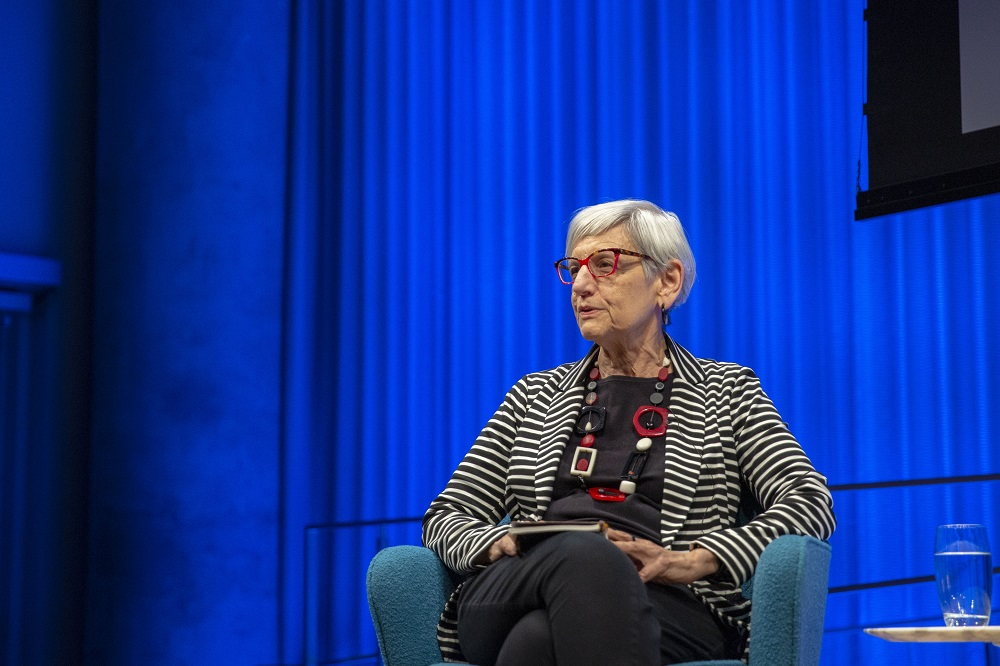 Harriet Senie, director of art history at the City College of New York, speaks onstage at the Museum Auditorium. She is seated in a chair in front of a curtain in the background that is illuminated blue.