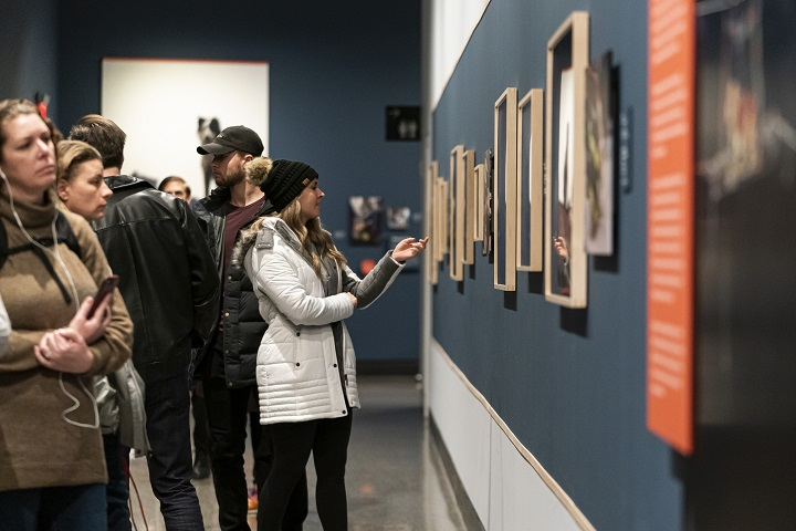 Museumgoers in winter coats stand in front of a blue wall, looking at framed photos in an exhibition. Some visitors are wearing audio guide headsets.