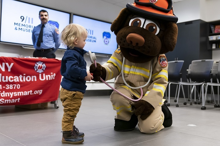 A man in a dog suit kneels and presses a plush stethoscope to a blond toddler's chest.