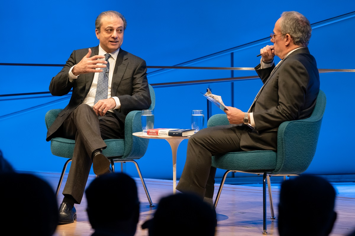 In this view from the audience, Preet Bharara, the former U.S. attorney for the Southern District of New York, speaks onstage as he gestures with his right hand. Moderator Clifford Chanin sits to Bharara's left holding a clipboard and putting a pen to his chin. A small white table with two glasses of water on it is between them. The wall behind them is lit blue. The silhouettes of audience members are in the foreground.