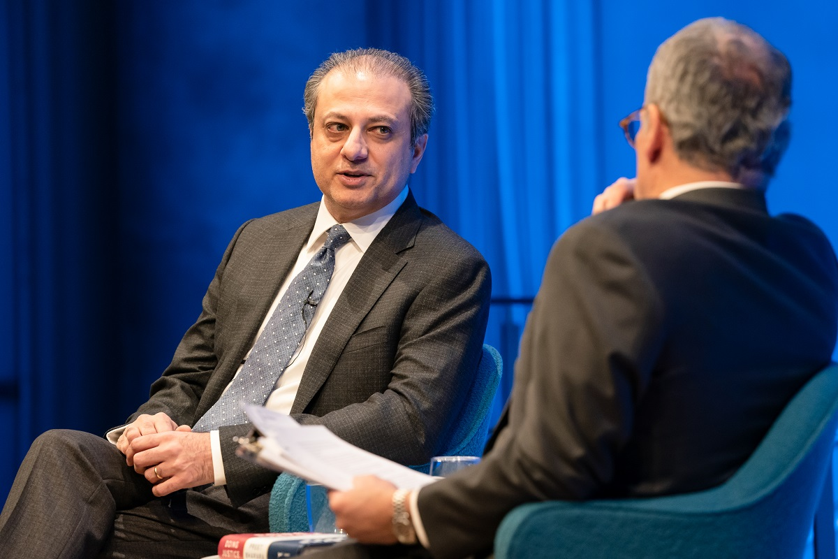 In this close-up view of the Museum Auditorium stage, Preet Bharara, the former U.S. attorney for the Southern District of New York, speaks with moderator Clifford Chanin, who is out of focus and has his back turned to the camera. A wall behind Bharara is lit blue from the stage lights.