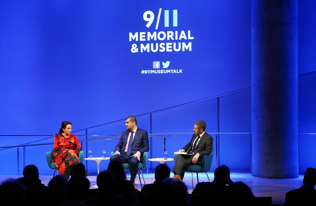 American Enterprise Institute scholar Karen E. Young, journalist Hassan Hassan, and the 9/11 Memorial & Museum's Noah Rauch sit onstage during a public program at the Museum's Auditorium. In this view from the audience, Young is speaking as Hassan and Rauch look towards her. About a dozen silhouetted audience members are in the foreground. Blue lights create a blue aura behind the participants onstage.