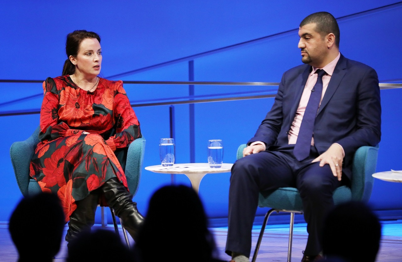 American Enterprise Institute scholar Karen E. Young sits with her legs crossed as she speaks onstage at the Museum Auditorium. A dress she is wearing with bright red flowers contrasts with the blue lights of the stage. To her left is journalist Hassan Hassan, who is listening with his hands on his legs. The heads of several audience members are silhouetted and out of focus in the foreground.