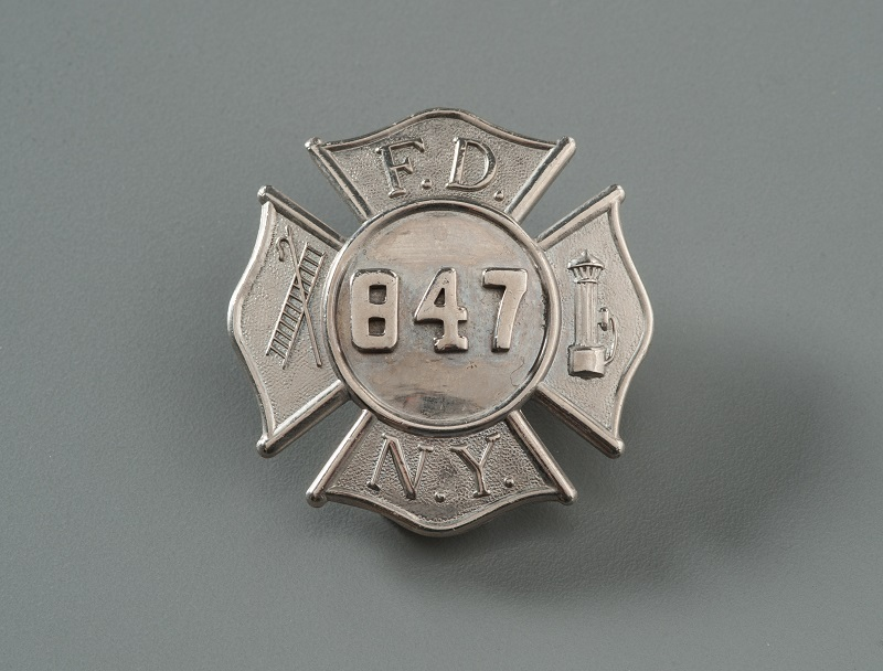 FDNY badge shaped as a Maltese cross with the numbers '847' in the center. The letters F D N Y and images of a hook, ladder, and fire hydrant fill the four cross arms.
