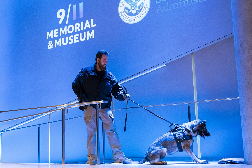 A dog handler performs a working dog demonstration in the 9/11 Museum auditorium.