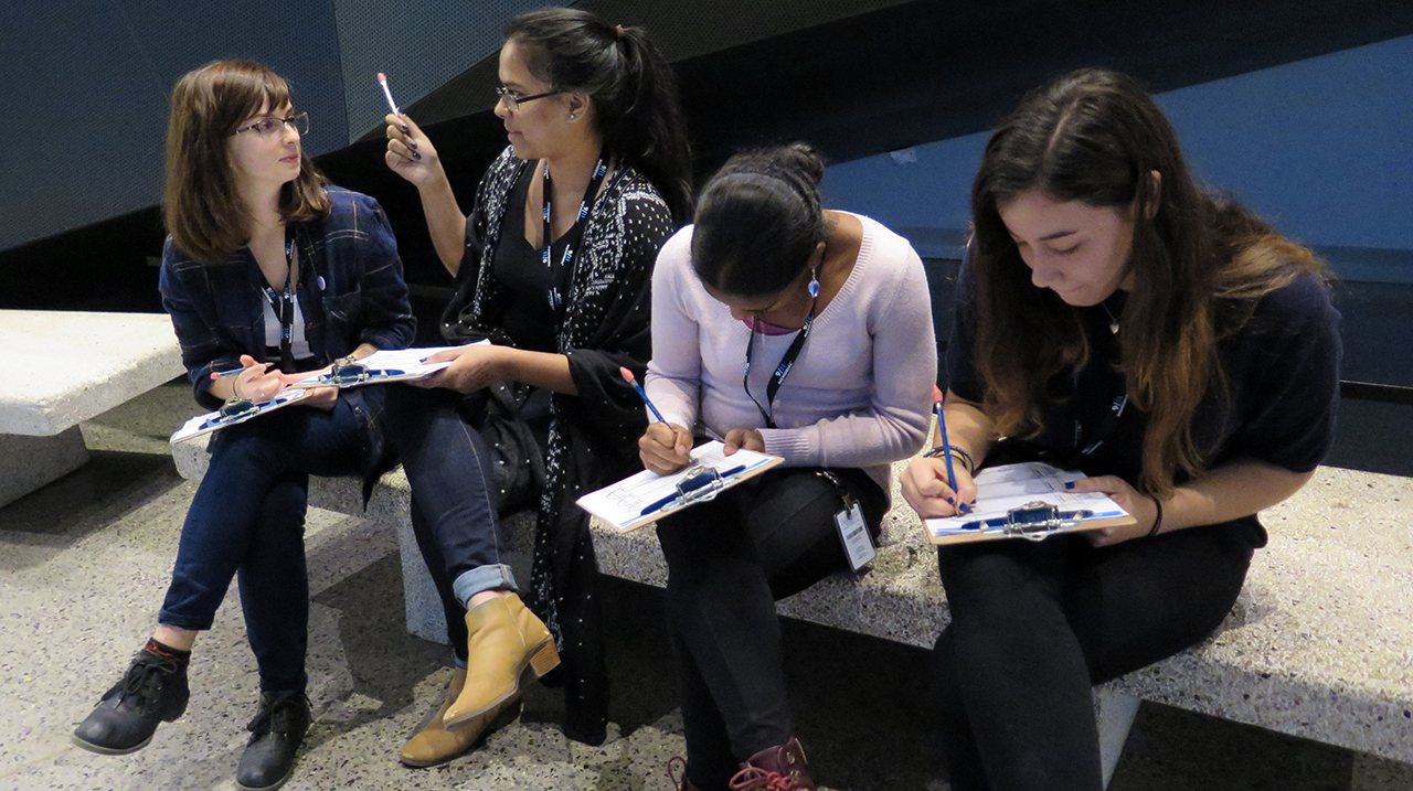 Four young women on a bench in the Museum. Two of them are writing on clipboards as the two others have a conversation.