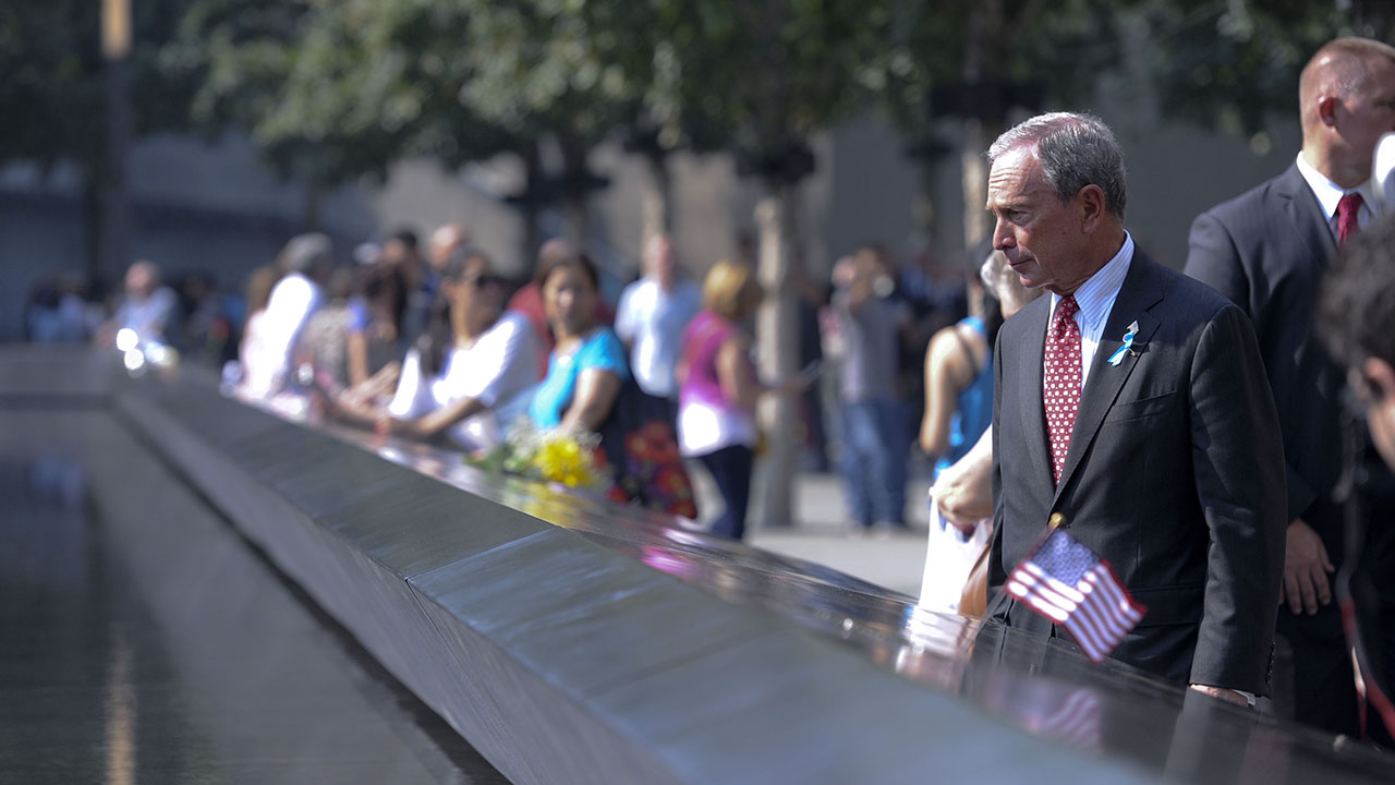 Michael Bloomberg, the chairman of the 9/11 Memorial & Museum, stands in a suit and tie beside a Memorial reflecting pool. In front of him, a bronze parapet runs along the border of the pool. A small American flag has been placed on the parapet.