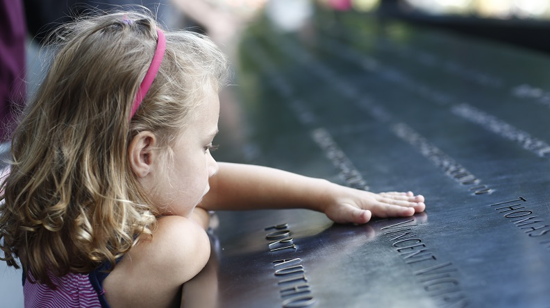 A young girl with blonde hair places her hand on a name etched in a bronze parapet at the Memorial.