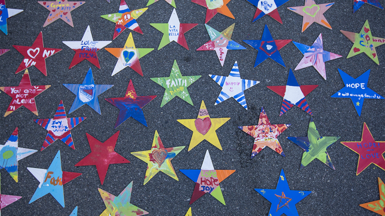 "Dozens of hand-painted, colorful paper stars are spread out on a gray surface. Children have colored various 9/11-themed tributes on each star. The more than thirty stars contain messages that read, ""hope,"" ""love,"" and ""I heart New York,"" among others."