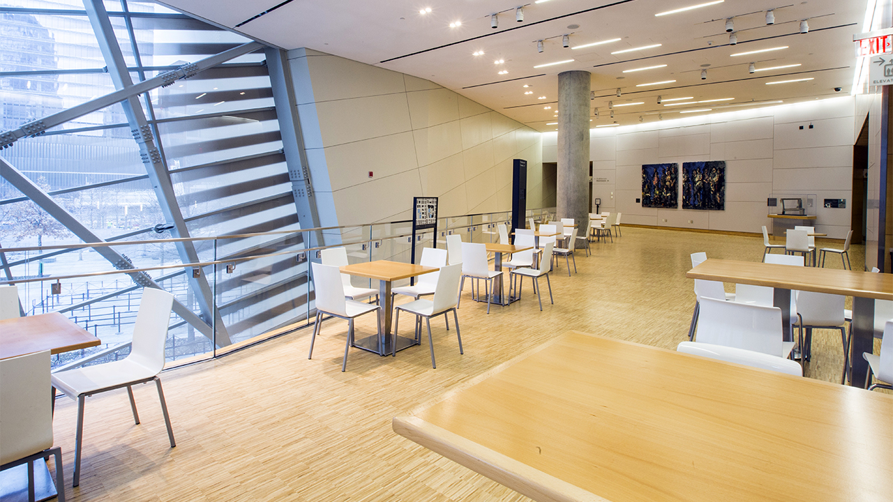 Small tables and chairs fill an empty atrium terrace at the museum Pavilion. The floors are hardwood and several pieces of art decorate the walls.