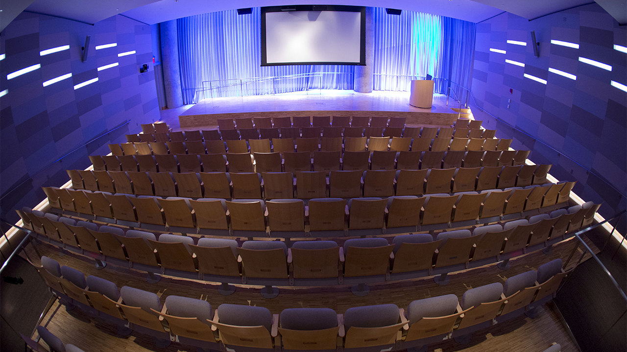 An empty Museum Auditorium is seen from above. Wooden theater seats are in the foreground. Further back, lights illuminate a stage, which has a lectern and lowered video screen.