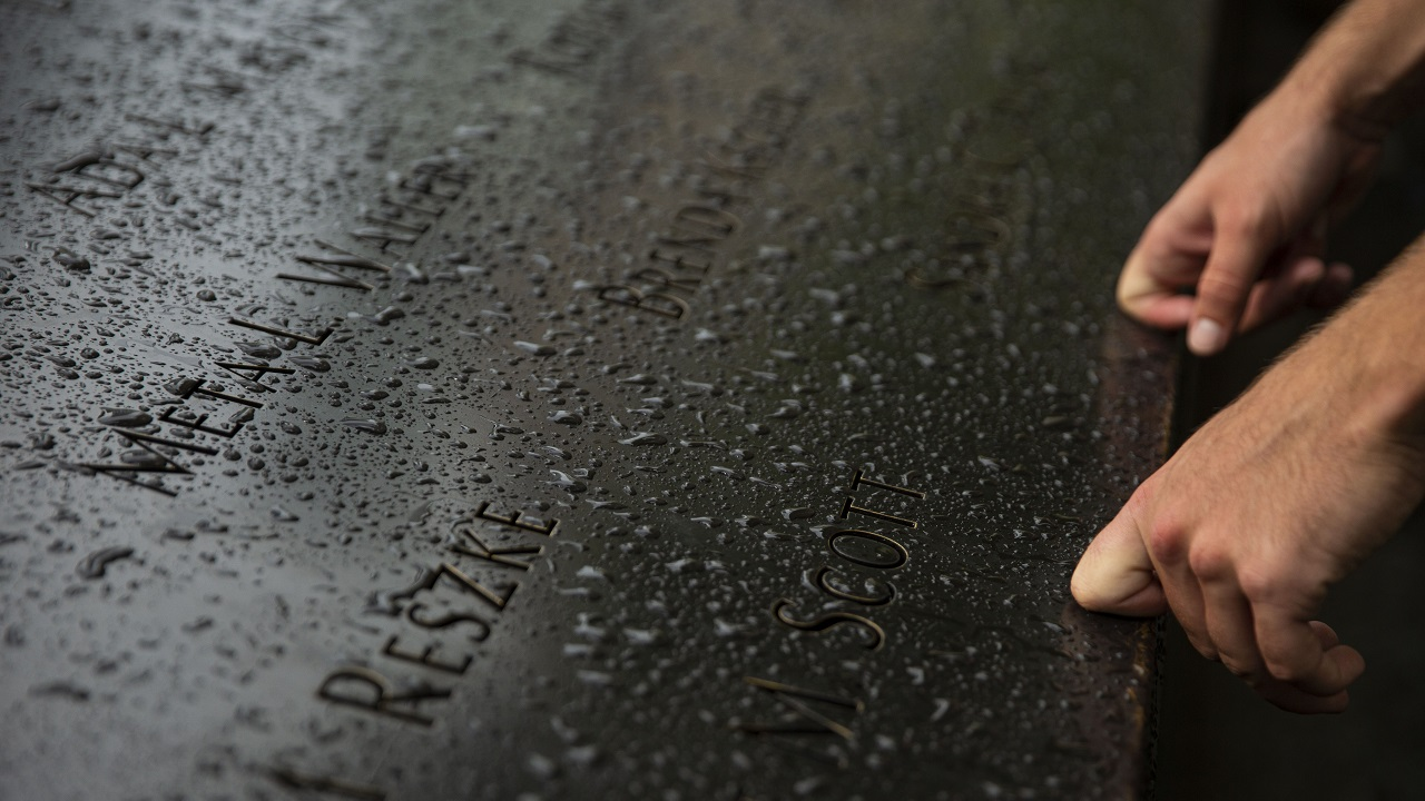 A person's hands are placed on a bronze parapet covered in raindrops. The knuckles of the index fingers are bent against the parapet next to two victims' names.
