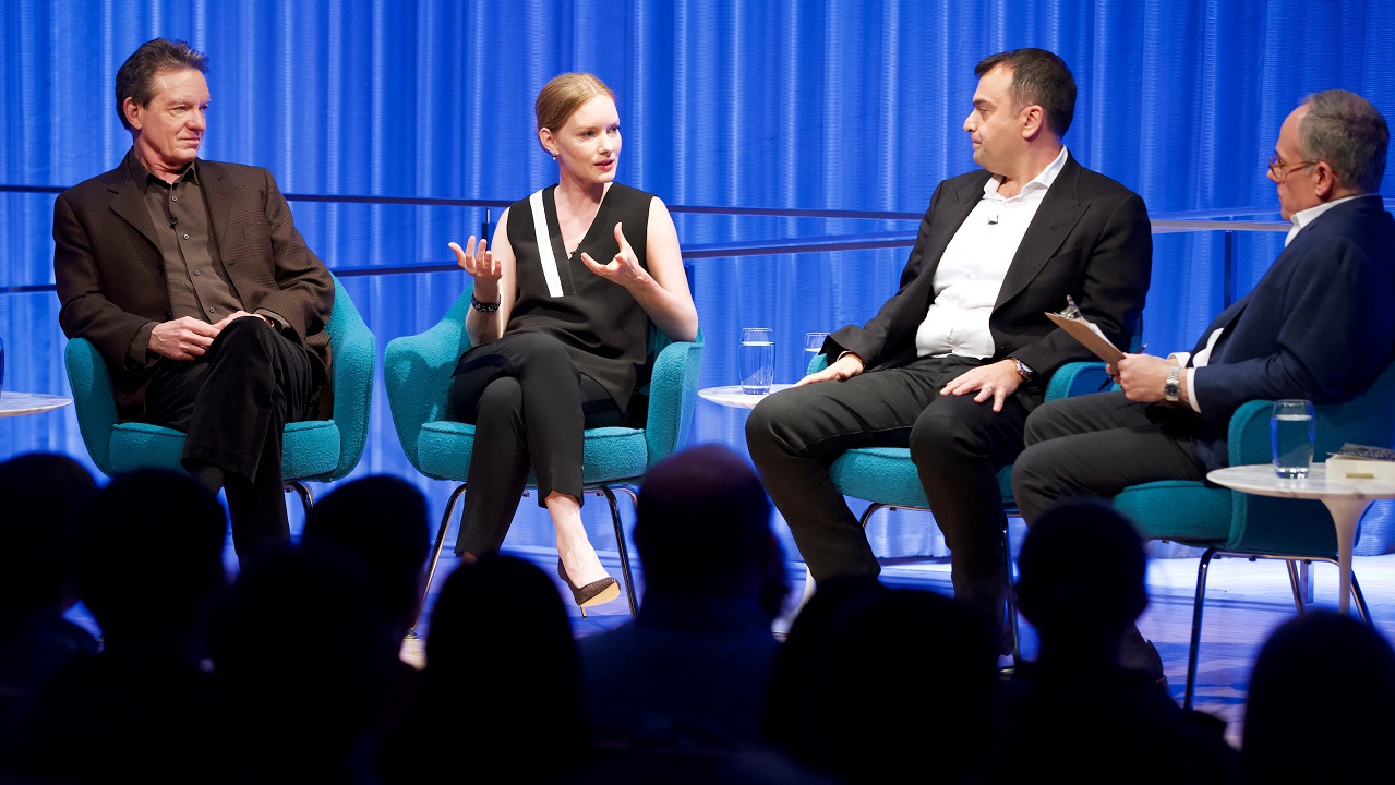 Three men and a woman take part in a moderated discussion on stage at the Museum. The woman is speaking, second from the left, as the three men listen. The black silhouettes of audience members are in the foreground.