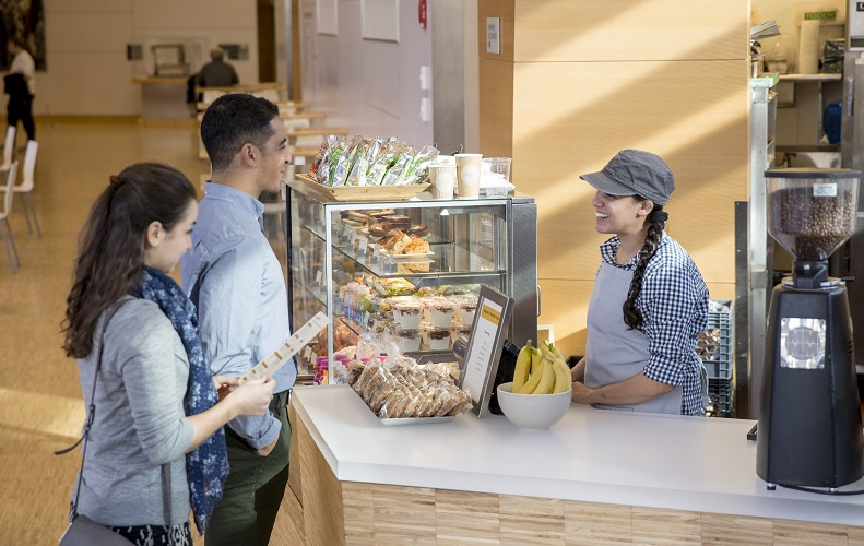 A woman behind a register greets a man and woman at the Pavilion Cafe. The two customers are looking through a menu as they speak with the cashier. Fruit, pastries and other food are in a display case.
