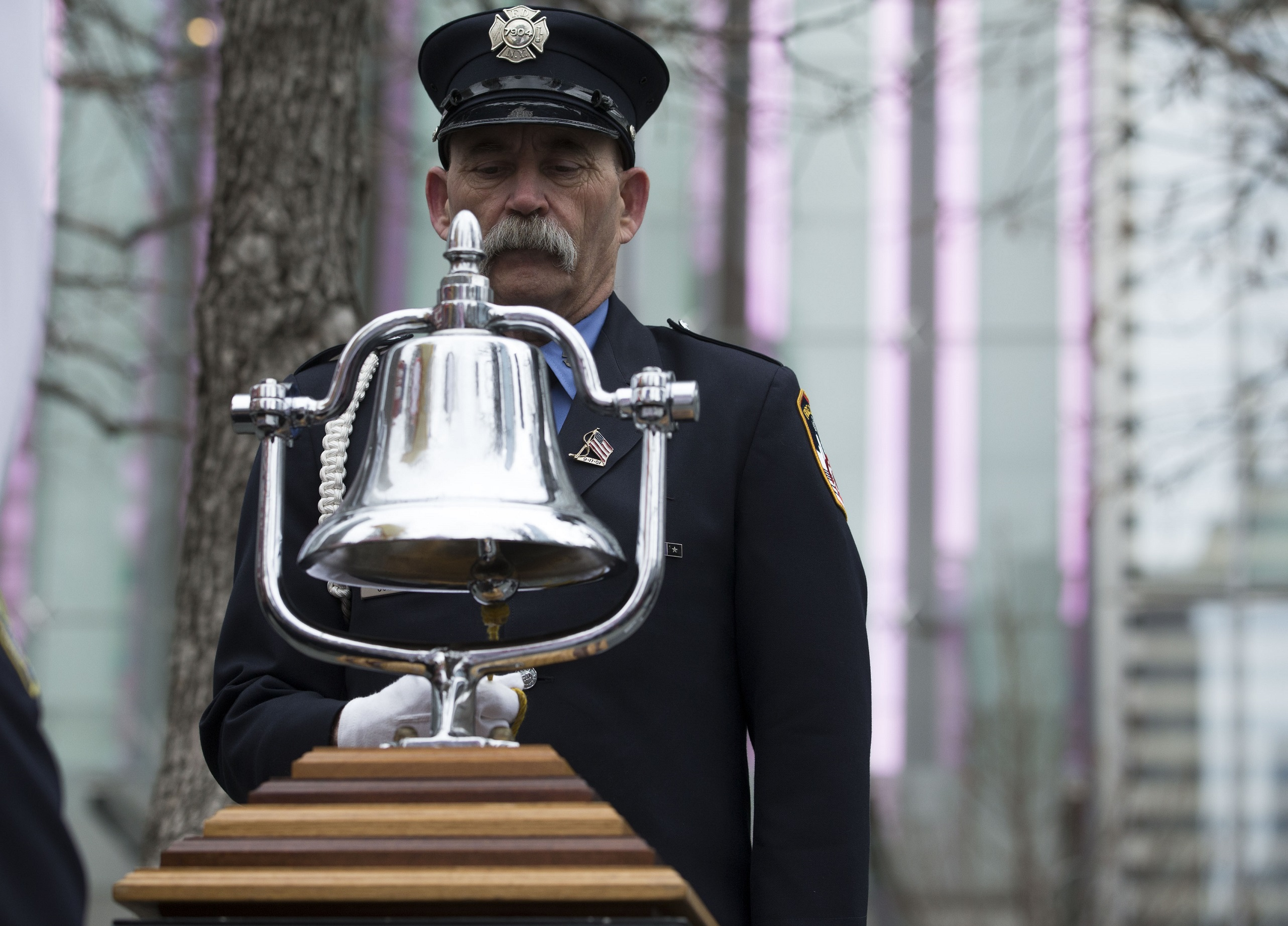 A mustachioed firefighter in a formal FDNY outfit rings a silver bell, marking the time the World Trade Center was bombed on February 26, 1993.
