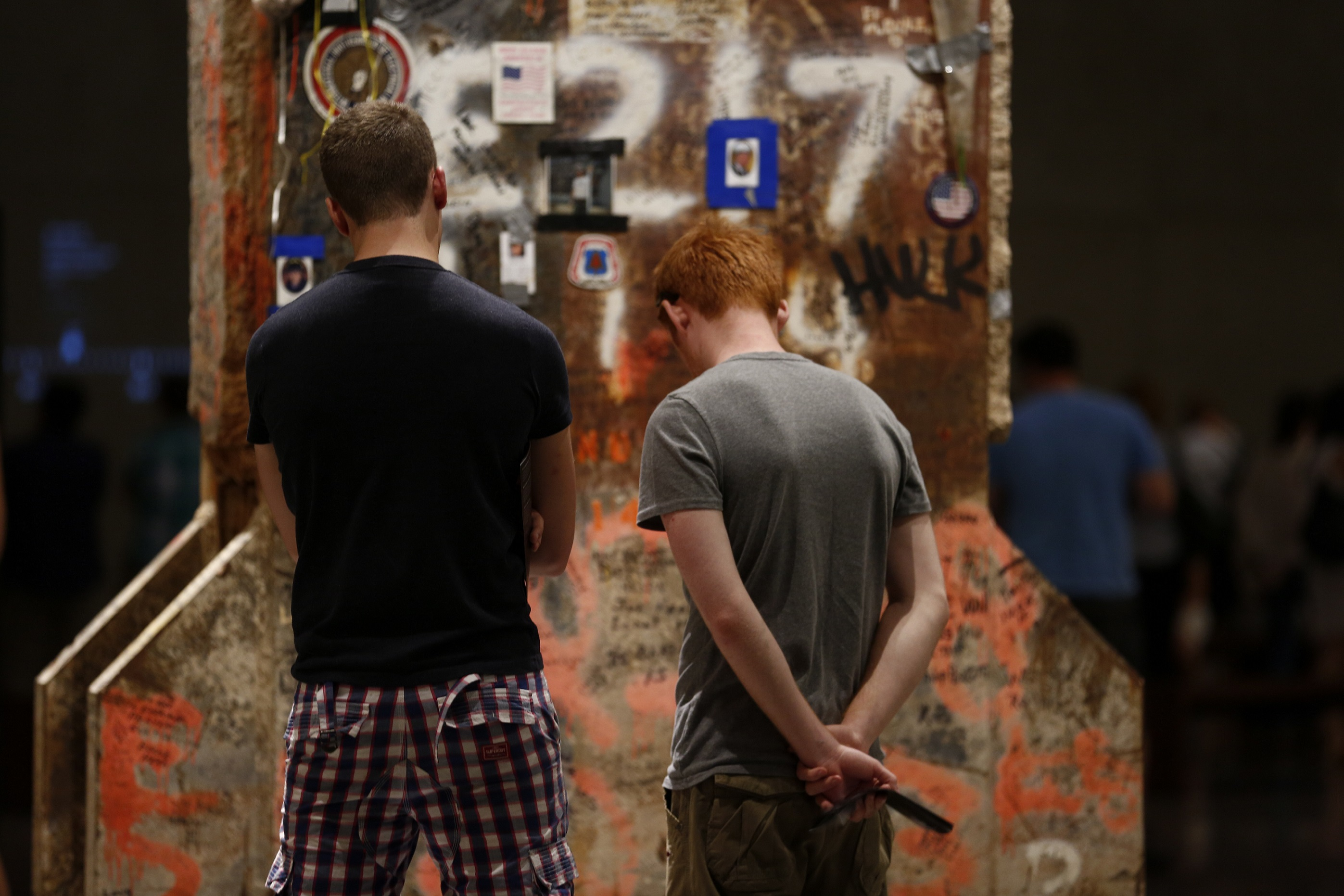 Two men face away as they look at the Last Column in Foundation Hall. The rusty column is covered in stickers, photos, handwritten messages, and other tributes, along with orange marking paint.