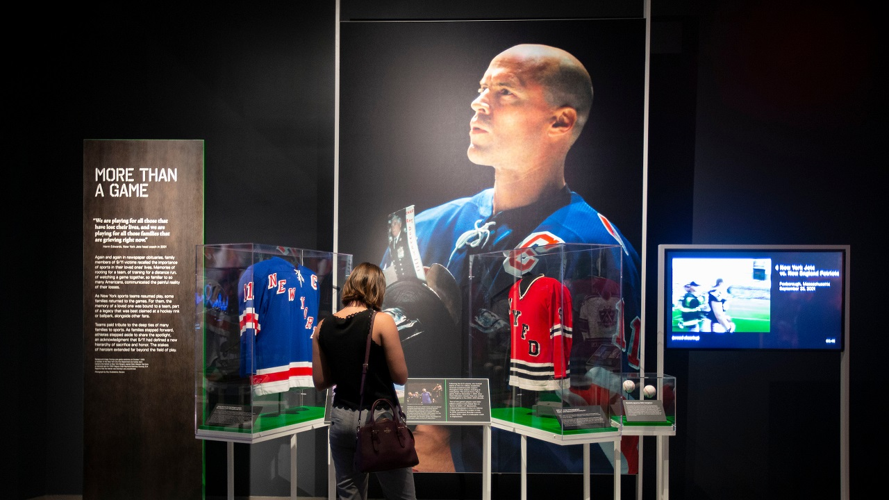 A large photograph of Rangers Captain Mark Messier appears beside two jerseys in the exhibition Comeback Season: Sports After 9/11.