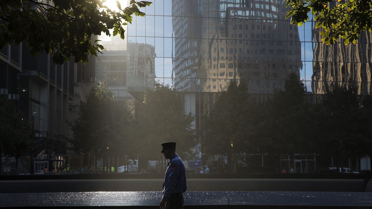 A firefighter in a formal outfit and hat looks at victims' names on a bronze parapet. Rays of sunlight come through a gap in buildings and shine down on him and a reflecting pool. In the darkened distance are trees and building facades.