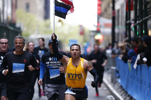 "A man in a yellow NYPD Running Club shirt holds up a ""thin blue line"" flag and an American flag as he runs in the 9/11 Memorial & Museum 5K Run/Walk.  Several other men are running beside him on a street in Manhattan. Onlookers watch from the sidewalk."