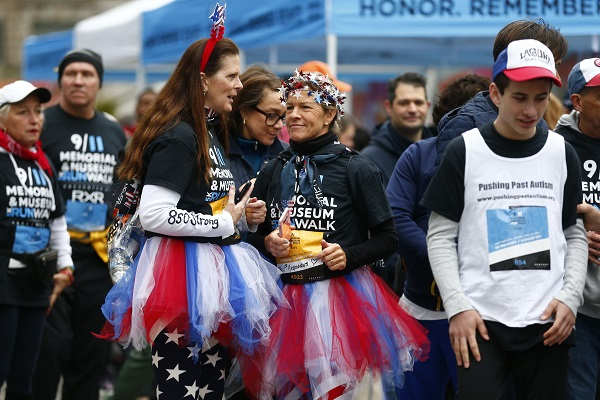 Two women wear patriotic outfits, including red, white, and blue tutus and American flag running pants, as they take part in the 9/11 Memorial & Museum 5K Run/Walk. Participants around them are also in running gear as they attend the event.